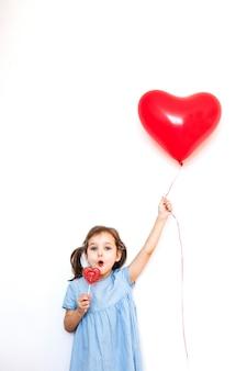 Mała dziewczynka trzymająca piękny czerwony balon w kształcie serca na prezent walentynkowy i lollipop w kształcie serca, kochanków, walentynek, rodziny i serca