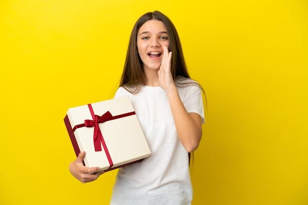 Mała dziewczynka trzymająca prezent na odosobnionym żółtym tle krzycząca z szeroko otwartymi ustami