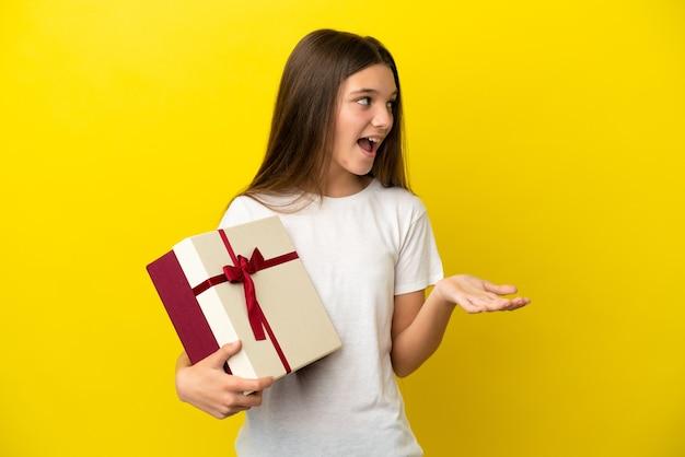 Mała dziewczynka trzymająca prezent na odosobnionym żółtym tle z wyrazem zaskoczenia, patrząc z boku