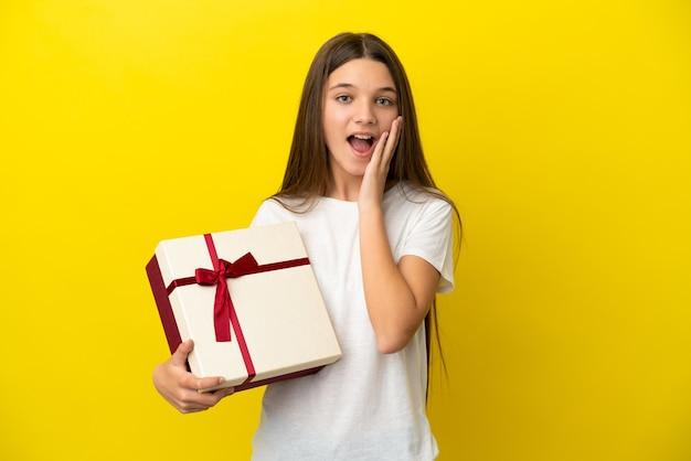 Mała dziewczynka trzymająca prezent nad odosobnioną żółtą ścianą z zaskoczeniem i zszokowanym wyrazem twarzy