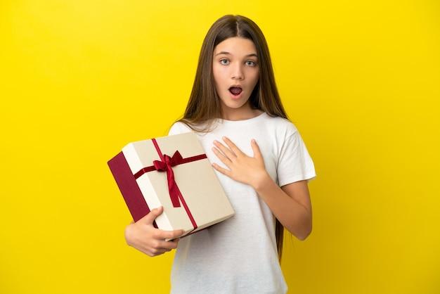 Mała dziewczynka trzymająca prezent nad odosobnioną żółtą ścianą zaskoczona i zszokowana, patrząc w prawo
