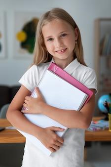 Mała dziewczynka trzymająca swoje książki