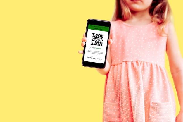 Mała dziewczynka trzymająca telefon komórkowy makieta cyfrowego świadectwa szczepień w jednej ręce i paszportu, maski i biletu w drugiej na żółtym tle