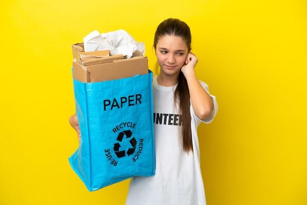 Mała dziewczynka trzymająca torbę do recyklingu pełną papieru do recyklingu nad odosobnioną żółtą powierzchnią sfrustrowana i zakrywająca uszy