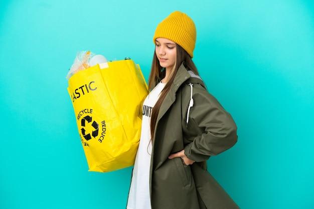 Mała dziewczynka trzymająca torbę pełną plastikowych butelek do recyklingu na odosobnionym niebieskim tle cierpi na ból pleców za wysiłek