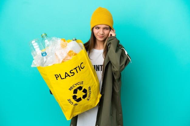 Mała dziewczynka trzymająca torbę pełną plastikowych butelek do recyklingu na odosobnionym niebieskim tle sfrustrowana i zakrywająca uszy
