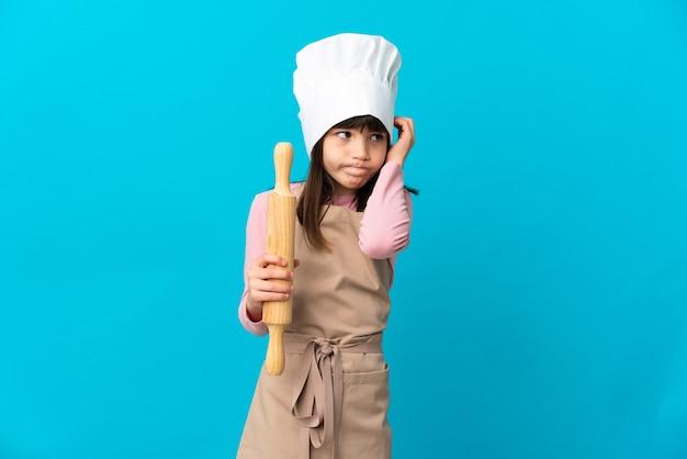 Mała dziewczynka trzymająca wałek do ciasta na białym tle na niebieskim tle sfrustrowana i zakrywająca uszy