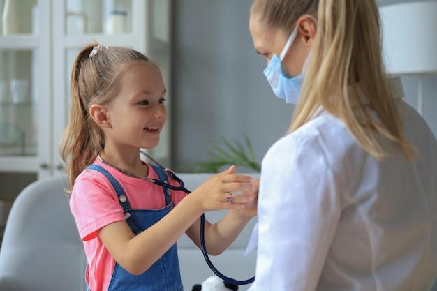 Mała dziewczynka u lekarza na badanie. dziecko osłuchuje bicie serca lekarza.