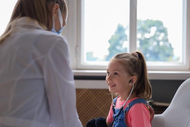 Mała dziewczynka u lekarza na badanie. lekarz żartobliwie sprawdza bicie serca pluszowego misia.
