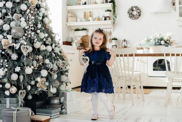 Mała dziewczynka ubiera świąteczny świerk i bawi się. spazjnik.