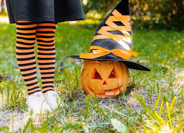 Mała dziewczynka ubrana jak czarownica grająca w jesiennym parku. dziecko bawiące się w halloween
