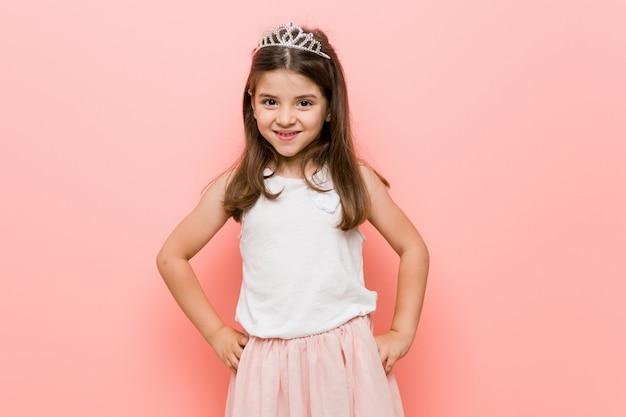Mała dziewczynka ubrana w księżniczkę wygląda pewnie, trzymając ręce na biodrach.