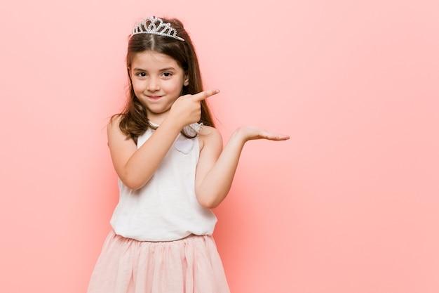 Mała dziewczynka ubrana w księżniczkę wygląda podekscytowany, trzymając miejsce na kopię na dłoni.
