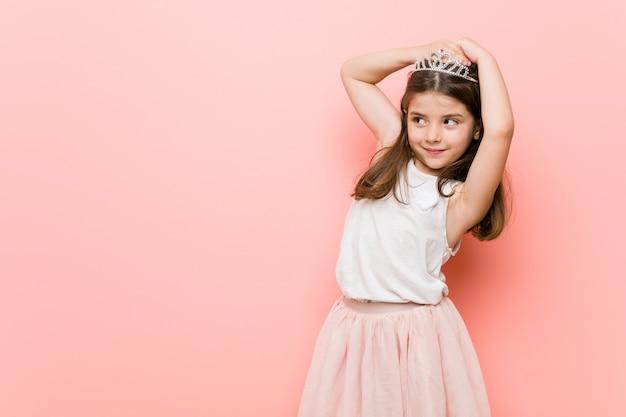 Mała dziewczynka ubrana w księżniczkę wygląda rozciągając ramiona, zrelaksowana pozycja.