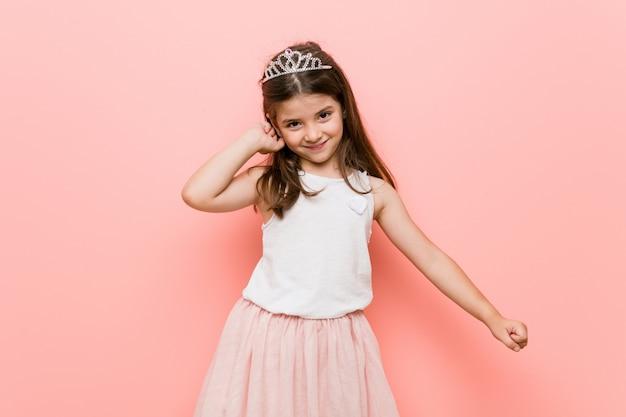 Mała dziewczynka ubrana w księżniczkę wygląda tańcząc i bawiąc się.
