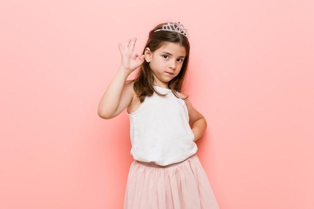 Mała dziewczynka ubrana w księżniczkę wygląda wesoło i pewnie, pokazując ok gest.