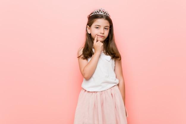 Mała dziewczynka ubrana w księżniczkę wygląda z ukosa z powątpiewaniem i sceptycznym wyrazem twarzy.
