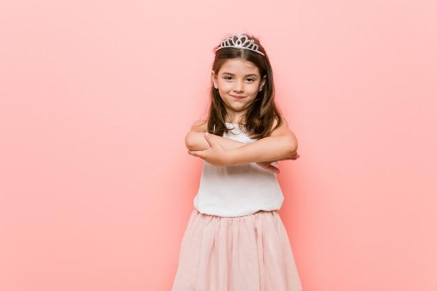 Mała dziewczynka ubrana w księżniczkę wygląda z uśmiechem skrzyżowanymi rękami.