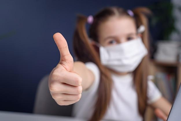 Mała dziewczynka ubrana w maskę do ochrony koronawirusa kowbojskiego i pokazuje kciuki do góry.