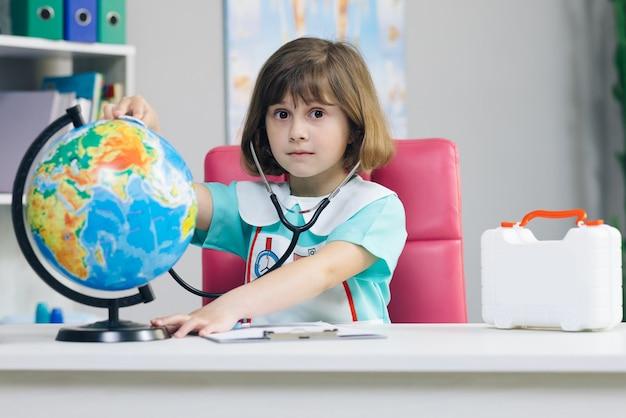 Mała dziewczynka ubrana w medyczną odzież ze stetoskopem w dłoniach bada i gra w uzdrawianie planety ziemia.