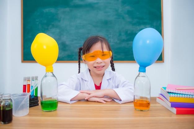 Mała dziewczynka ubrana w płaszcz i trzymając mikroskop