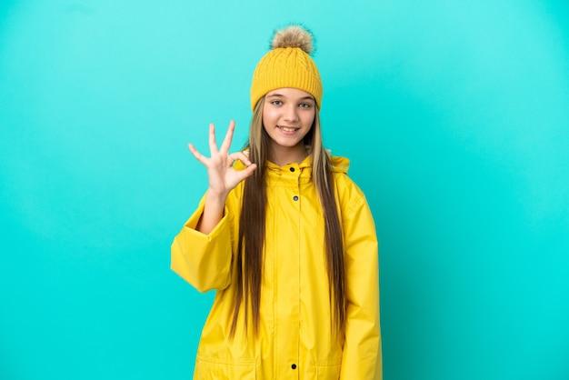 Mała dziewczynka ubrana w płaszcz przeciwdeszczowy na na białym tle niebieskim tle pokazując znak ok palcami