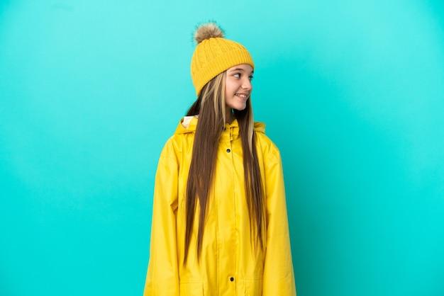 Mała dziewczynka ubrana w przeciwdeszczowy płaszcz na odosobnionym niebieskim tle patrząc z boku