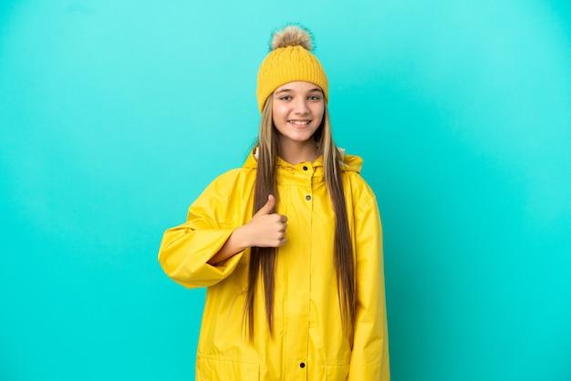 Mała dziewczynka ubrana w przeciwdeszczowy płaszcz na odosobnionym niebieskim tle, pokazująca gest kciuka w górę