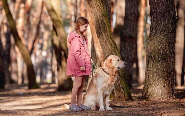 Mała dziewczynka ubrana w różowy płaszcz spacerująca z psem golden retriever w drewnie
