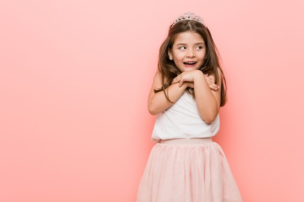 Mała dziewczynka ubrana w strój księżniczki trzyma ręce pod brodą i patrzy radośnie na bok.