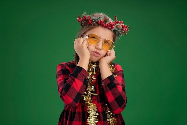 Mała dziewczynka ubrana w świąteczny wieniec w kraciastej sukience z blichtrem na szyi, patrząc na kamerę z zmieszanym wyrazem twarzy, stojąc na zielonym tle z rękami na twarzy