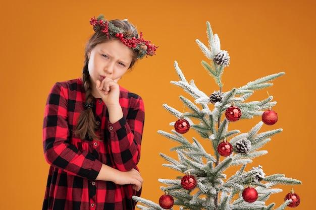 Mała dziewczynka ubrana w świąteczny wieniec w kraciastej sukience z ręką na brodzie, myśląca z poważną twarzą, stojąca obok choinki nad pomarańczową ścianą