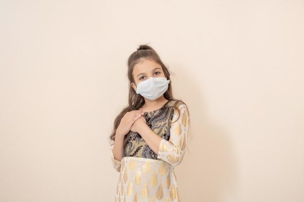 Mała dziewczynka ubrana w tradycyjną pakistańską sukienkę i maskę oraz świętująca ramadan kareem.