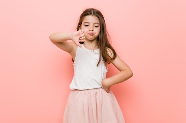 Mała dziewczynka ubrana w wygląd księżniczki pokazujący gest niechęci, kciuki w dół
