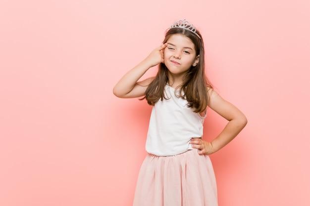 Mała dziewczynka ubrana w wygląd księżniczki pokazujący gest rozczarowania z palcem wskazującym.