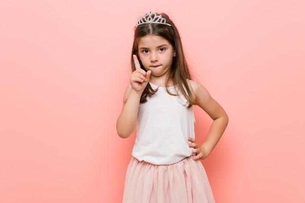 Mała dziewczynka ubrana w wygląd księżniczki pokazuje numer jeden z palcem.