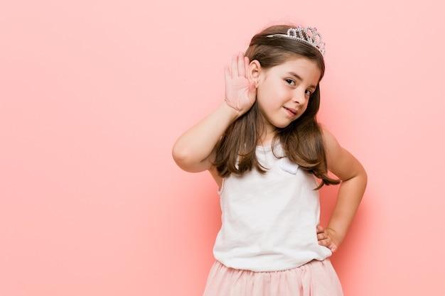 Mała dziewczynka ubrana w wygląd księżniczki próbuje słuchać plotek.