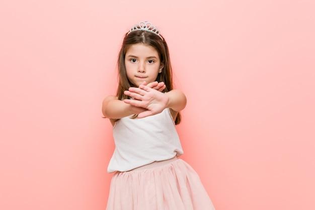 Mała dziewczynka ubrana w wygląd księżniczki robi gest odmowy