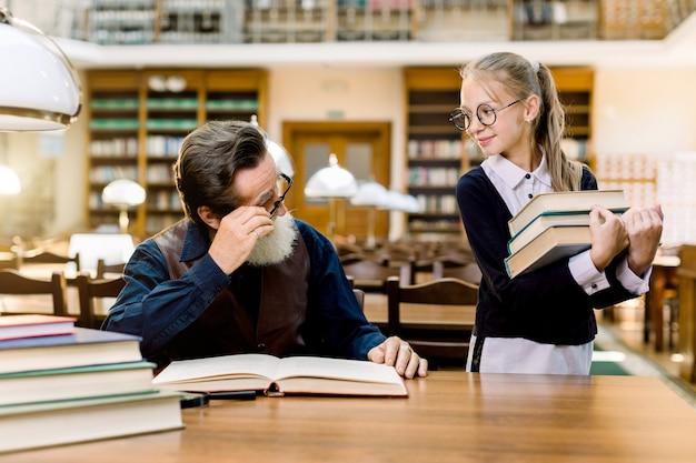 Mała dziewczynka uczeń uczeń trzyma w ręku wiele książek i patrzy na swojego starszego brodatego nauczyciela siedzącego przy stole i czytającego książki w zabytkowej bibliotece