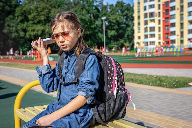 Mała dziewczynka, uczennica szkoły podstawowej w okularach przeciwsłonecznych, dzwoni, tylko rozmawia, komunikuje się.