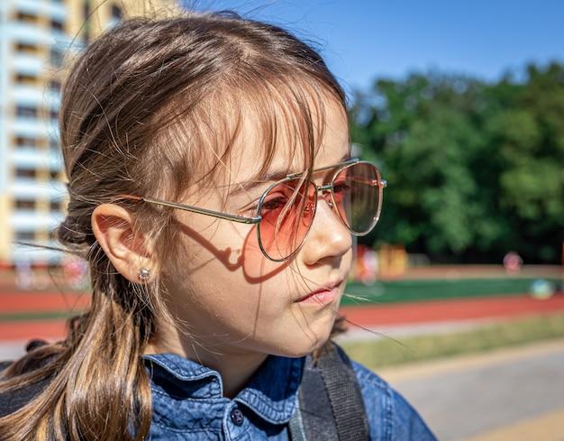 Mała dziewczynka, uczennica szkoły podstawowej w okularach przeciwsłonecznych, zbliżenie na zewnątrz.