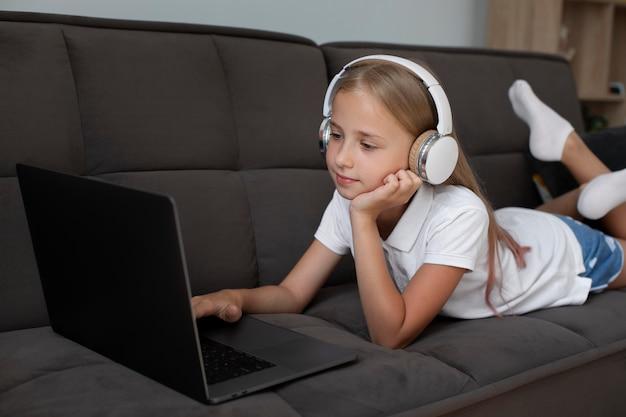 Mała dziewczynka uczestnicząca w zajęciach online podczas korzystania ze słuchawek