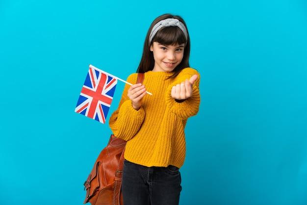 Mała dziewczynka uczy się angielskiego na białym tle na niebieskim tle robienia pieniędzy gest