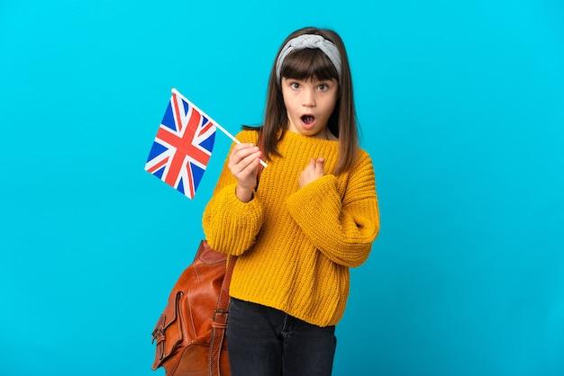 Mała dziewczynka uczy się angielskiego na białym tle na niebieskim tle z niespodzianką wyrazem twarzy