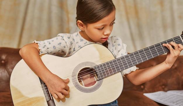 Mała dziewczynka uczy się grać na gitarze w domu