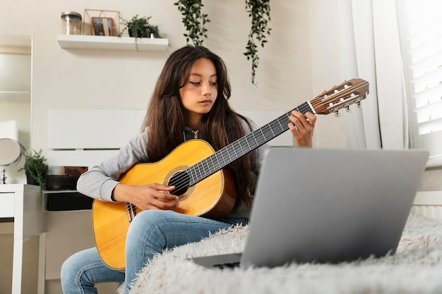 Mała dziewczynka uczy się grać na gitarze
