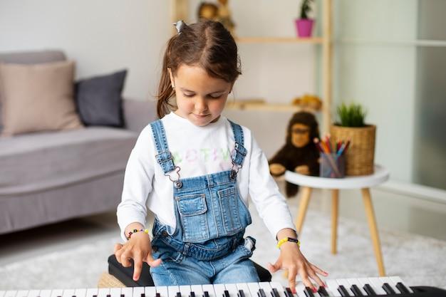 Mała dziewczynka uczy się grać na pianinie