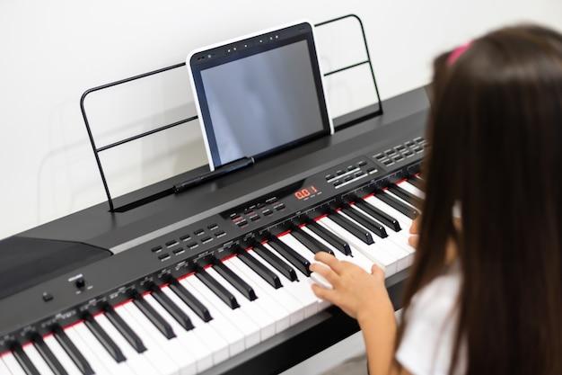 Mała dziewczynka uczy się gry na pianinie podczas lekcji wideo