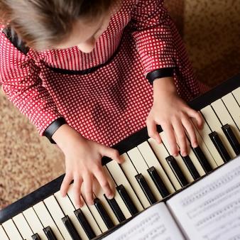 Mała dziewczynka uczy się gry na pianinie w domu