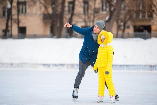 Mała dziewczynka uczy się jeździć na łyżwach z ojcem na lodowisku na zewnątrz